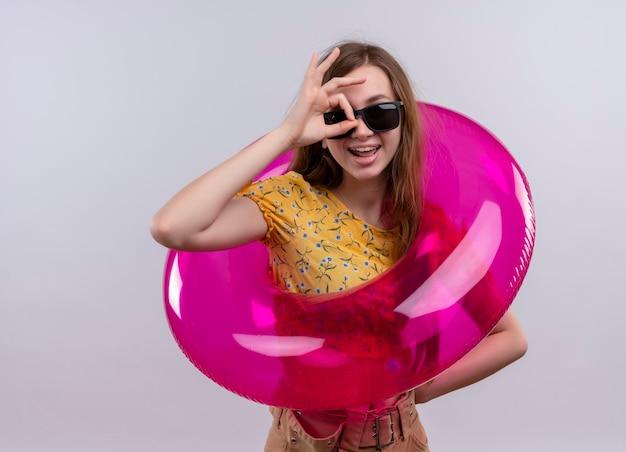 Radosna młoda dziewczyna w okularach przeciwsłonecznych i pierścieniu do pływania robi gest wyglądu na odosobnionej białej przestrzeni z miejsca na kopię