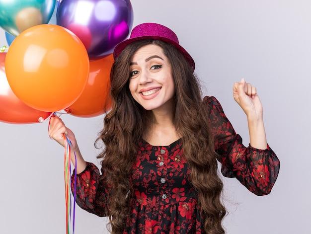 Radosna młoda imprezowa dziewczyna w imprezowym kapeluszu trzymająca balony zaciskające pięść na białej ścianie