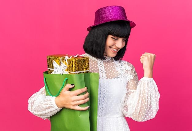Radosna młoda imprezowa dziewczyna w imprezowym kapeluszu trzymająca pakiet prezentów w papierowej torbie, patrząca w dół, robiąca gest tak na różowej ścianie