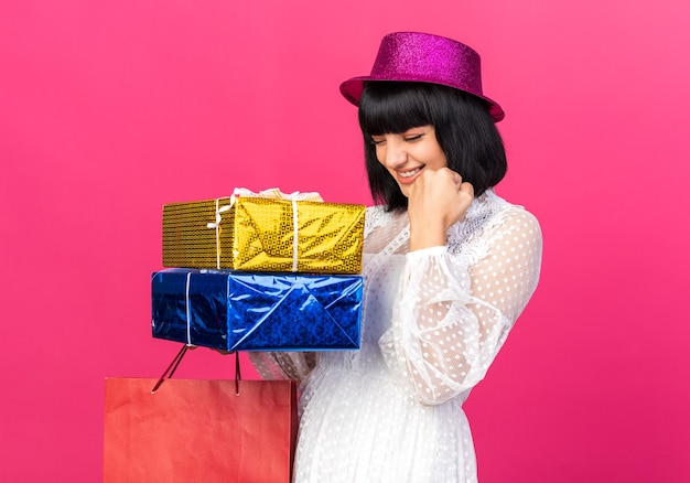 """Radosna młoda imprezowa dziewczyna w imprezowym kapeluszu, trzymająca papierową torbę i paczki z prezentami, robiąca gest """"tak"""" z zamkniętymi oczami na różowej ścianie"""