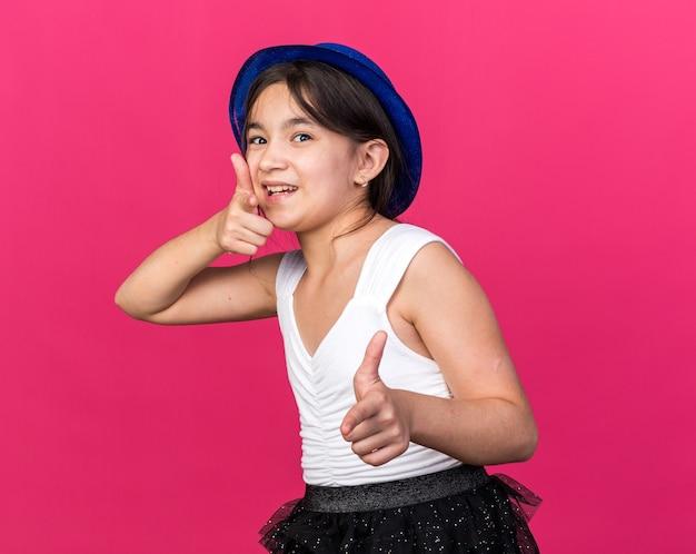Radosna młoda kaukaska dziewczyna w niebieskim kapeluszu imprezowym wskazującym na różowej ścianie z miejscem na kopię