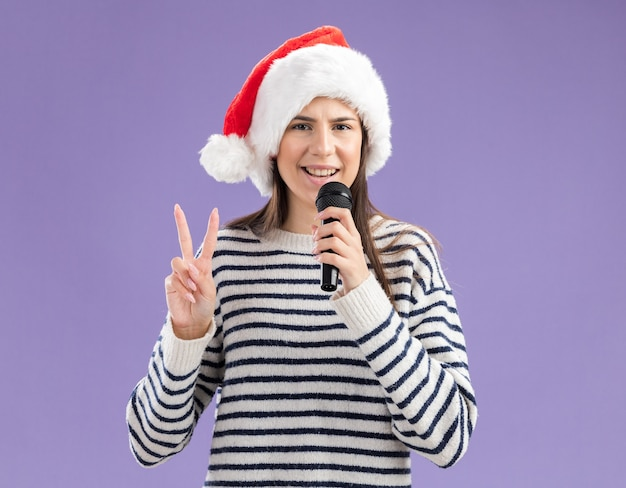 Radosna młoda kaukaska dziewczyna w santa hat trzyma mikrofon i gestykuluje znak zwycięstwa na fioletowej ścianie z kopią przestrzeni
