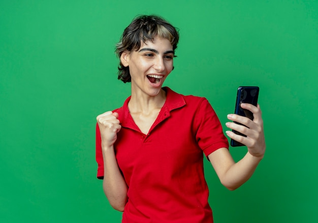 Radosna młoda kaukaska dziewczyna z fryzurą pixie trzyma i patrzy na telefon komórkowy z zaciśniętą pięścią