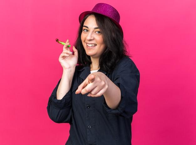 Radosna młoda kaukaska kobieta w imprezowym kapeluszu, trzymająca róg imprezowy, patrząca i wskazująca z przodu na różowej ścianie