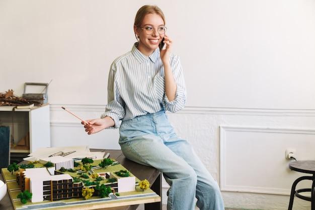 Radosna młoda kobieta architekt rozmawia przez telefon komórkowy podczas projektowania szkicu z modelem domu w miejscu pracy