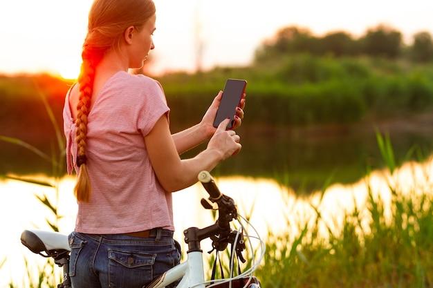 Radosna młoda kobieta, jazda na rowerze przy promenadzie nad rzeką i łąką.