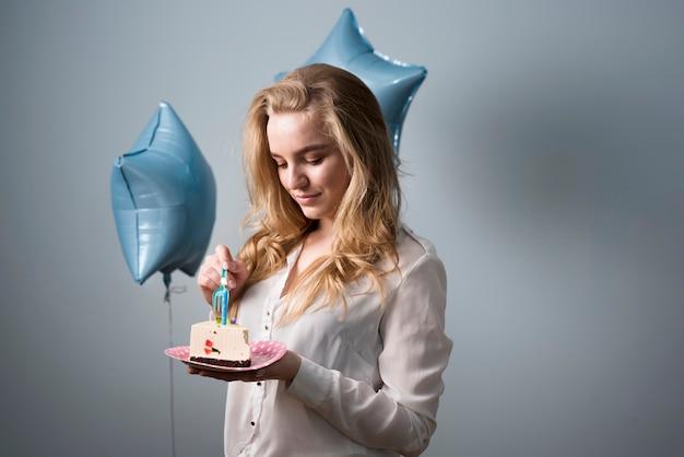 Radosna młoda kobieta je urodzinowego tort