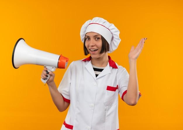Radosna młoda kobieta kucharz w mundurze szefa kuchni trzymając głośnik i pokazując pustą rękę na pomarańczowym tle