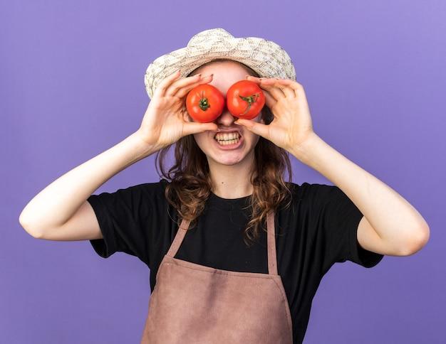 Radosna młoda kobieta ogrodniczka w kapeluszu ogrodniczym trzymająca gest pokazujący wygląd z pomidorami
