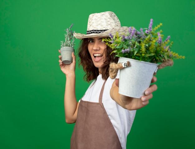 Radosna młoda kobieta ogrodniczka w mundurze na sobie kapelusz ogrodniczy, trzymając kwiaty w doniczkach