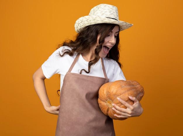 Radosna młoda kobieta ogrodnik w mundurze na sobie kapelusz ogrodniczy trzyma i patrzy na dyni na białym tle na pomarańczowej ścianie