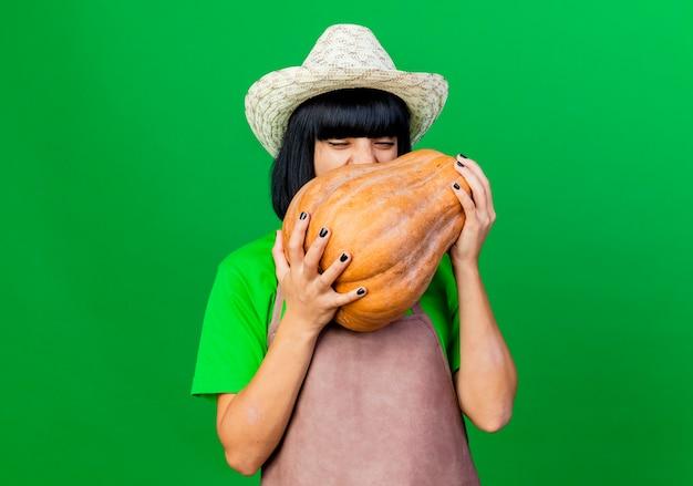 Radosna młoda kobieta ogrodnik w mundurze na sobie kapelusz ogrodniczy, trzymając i próbuje ugryźć dynię