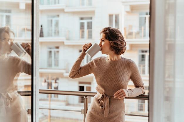 Radosna młoda kobieta pije kawę i patrzy na miasto. kryty zdjęcie zadowolonej kręconej dziewczyny w brązowej sukience spędzającej poranek na balkonie.