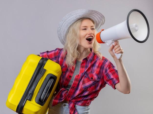 Radosna młoda kobieta podróżująca w czerwonej koszuli w kapeluszu, trzymając walizkę, mówi przez głośniki na odosobnionej białej ścianie