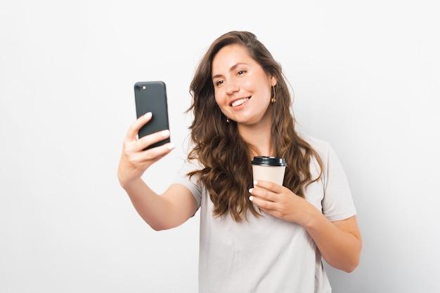 Radosna młoda kobieta robi selfie trzymając filiżankę kawy na wynos.