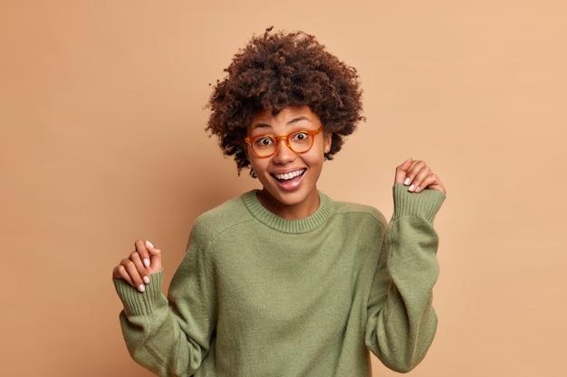 Radosna młoda kobieta tańczy na beżowej ścianie, trzymając ręce w górze, a rytm muzyki na imprezie wyraża pozytywne emocje odizolowane na brązowej ścianie
