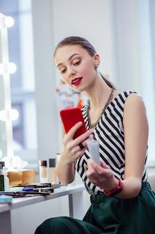 Radosna młoda kobieta trzymająca czerwony smartfon podczas robienia zdjęć kremu