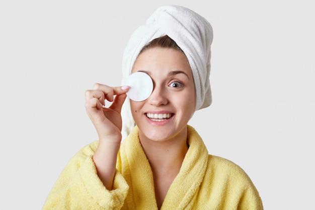 Radosna młoda kobieta usuwa makijaż bawełnianym dyskiem, ma zębaty uśmiech, używa kosmetyków, nosi ciepłą żółtą szatę, izolowaną na białej ścianie. ładna pani używa wacików, dba o swoją skórę.