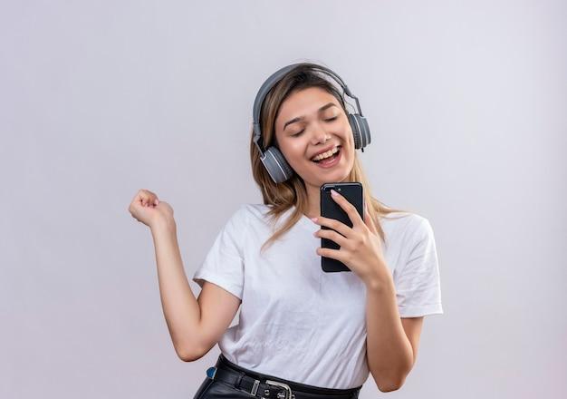 Radosna młoda kobieta w białej koszulce, nosząca słuchawki, śpiewa, słuchając muzyki z telefonu na białej ścianie