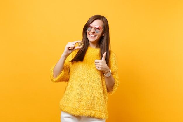 Radosna młoda kobieta w okularach serca pokazując kciuk do góry, trzymając bitcoin, metalowe monety złotego koloru, przyszła waluta na białym tle na żółtym tle. ludzie szczere emocje, styl życia. powierzchnia reklamowa.