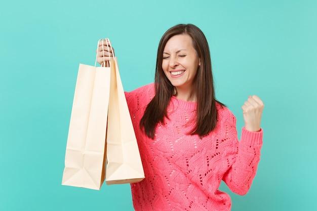 Radosna młoda kobieta w różowym swetrze z dzianiny robi gest zwycięzcy, trzymając pakiety torby z zakupami po zakupach na białym tle na tle niebieskiej ściany. koncepcja życia ludzi. makieta miejsca na kopię.