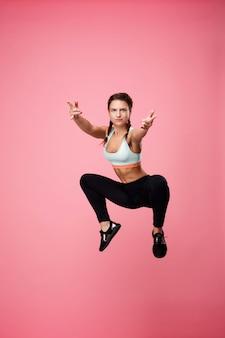 Radosna młoda kobieta w stroju sportowym moda skoki skaczący w górę