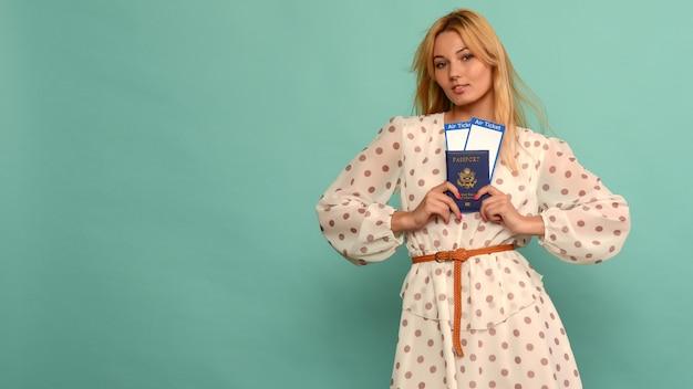 Radosna młoda kobieta w sukience w kropki trzyma bilety lotnicze z paszportem na niebieskim tle. cieszy się z wznowienia turystyki po pandemii koronowirusa.