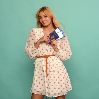 Radosna młoda kobieta w sukience w kropki trzyma bilety lotnicze z paszportem na niebieskim tle.