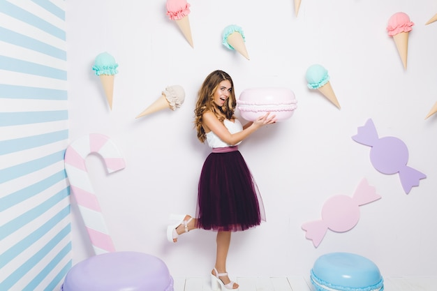 Radosna młoda kobieta w tiulowej spódnicy bawi się z dużym makaronikiem wśród słodyczy. pastelowe kolory, lody, szczęście, babeczki, uśmiechnięte, zaskoczone, figlarne.