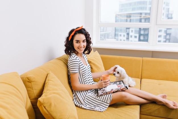 Radosna młoda kobieta z obciętymi włosami brunetki w sukience chłodzenie z psem na kanapie w nowoczesnym mieszkaniu. czytanie gazet, filiżanka herbaty, wygoda, przytulny czas w domu ze zwierzętami