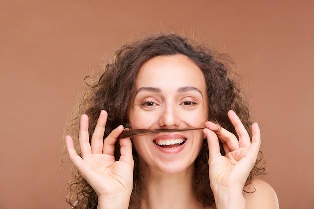 Radosna młoda kobieta z zębatym uśmiechem, trzymając wiązkę włosów między ustami i nosem, bawiąc się i wyrażając radość