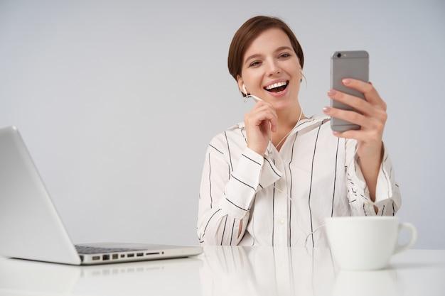 Radosna młoda krótkowłosa brunetka kobieta z przypadkową fryzurą, trzymając telefon komórkowy w uniesionej ręce i prowadząc rozmowę wideo, uśmiechając się radośnie siedząc na białym