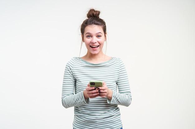 Radosna młoda ładna brązowowłosa kobieta z naturalnym makijażem, uśmiechnięta radośnie, patrząc z przodu, stojąca nad białą ścianą z telefonem komórkowym w dłoniach
