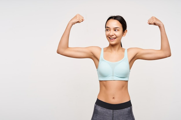 Radosna młoda ładna brunetka szczupła kobieta ubrana w sportowe ubrania, pokazująca swoje silne bicepsy i spoglądająca radośnie na bok, pozując na białej ścianie