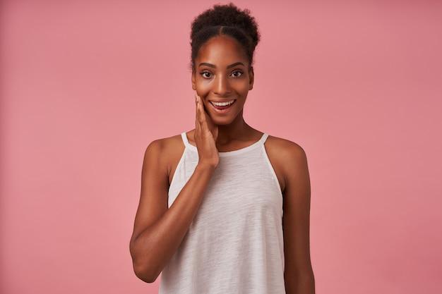 Radosna młoda ładna brunettened dama z przypadkową fryzurą unosząca emocjonalnie rękę, patrząc radośnie z przodu z szerokim uśmiechem, pozująca na różowej ścianie