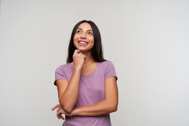 Radosna młoda ładna ciemnowłosa kobieta z naturalnym makijażem delikatnie dotykająca podbródka uniesioną ręką i uśmiechająca się przyjemnie, patrząc w górę, odizolowana