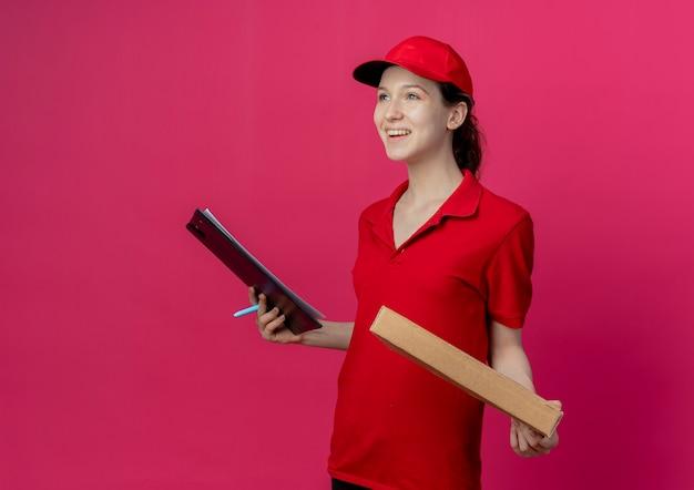 Radosna młoda ładna dziewczyna dostawy w czerwonym mundurze i czapce stojąca w widoku profilu, trzymając paczkę pizzy i schowek z piórem, patrząc prosto na białym tle na szkarłatnym tle z miejscem na kopię