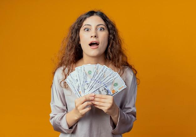 Radosna młoda ładna dziewczyna trzyma pieniądze