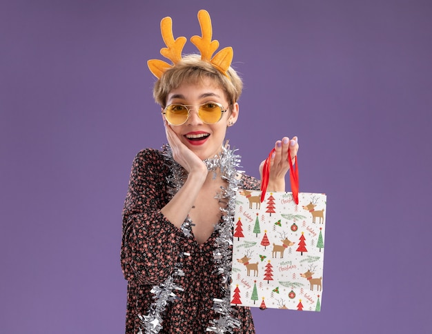 Radosna młoda ładna dziewczyna ubrana w opaskę z poroża renifera i blichtrową girlandę wokół szyi w okularach trzymająca świąteczny prezent torba trzymająca rękę na twarzy odizolowana na fioletowej ścianie z kopią miejsca