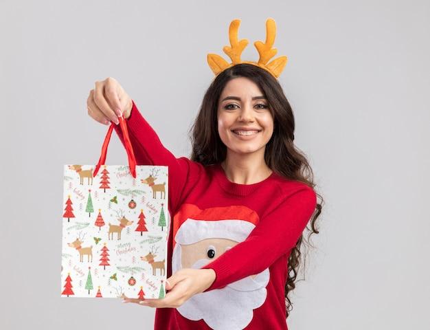Radosna młoda ładna dziewczyna ubrana w opaskę z poroża renifera i sweter świętego mikołaja wyciągająca torbę z prezentami świątecznymi w kierunku aparatu patrząc