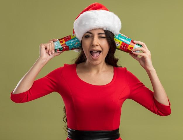 Radosna młoda ładna dziewczyna w kapeluszu świętego mikołaja trzymająca świąteczne filiżanki kawy obok uszu słuchająca rozmów mrugających na białym tle na oliwnej ścianie