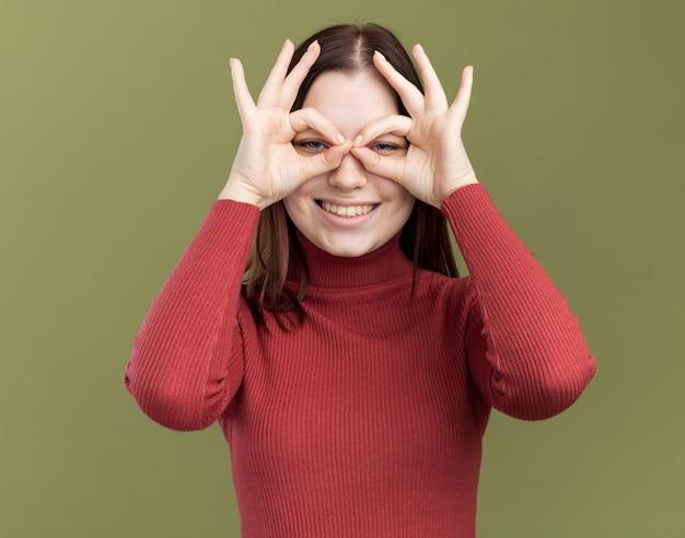 Radosna młoda ładna dziewczyna w okularach przeciwsłonecznych robi gest spojrzenia za pomocą rąk jako lornetki