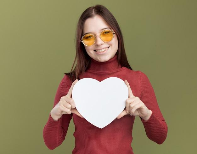 Radosna młoda ładna dziewczyna w okularach przeciwsłonecznych trzymająca znak serca odizolowana na oliwkowozielonej ścianie