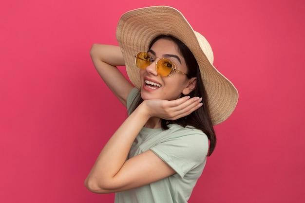 Radosna młoda ładna kaukaska dziewczyna w kapeluszu plażowym i okularach przeciwsłonecznych, stojąca w widoku profilu, trzymając ręce w pobliżu głowy odizolowanej na różowej ścianie z kopią przestrzeni