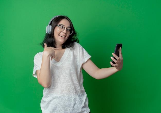 Radosna młoda ładna kaukaska dziewczyna w okularach i słuchawkach, trzymająca i patrząca na telefon komórkowy i wskazująca na siebie