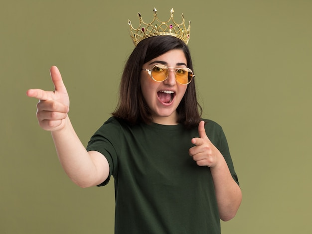 Radosna młoda ładna kaukaska dziewczyna w okularach przeciwsłonecznych z koroną skierowaną na bok z dwiema rękami odizolowanymi na oliwkowozielonej ścianie z kopią przestrzeni