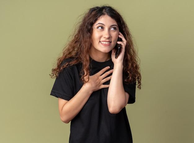Radosna młoda ładna kaukaska kobieta rozmawia przez telefon, patrząc na bok, wykonując gest dziękuję
