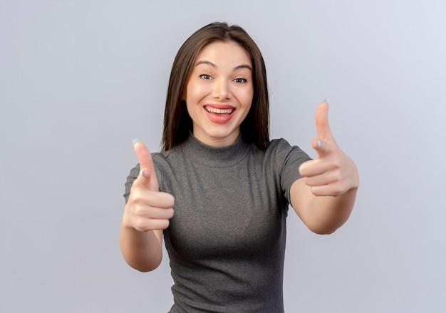 Radosna młoda ładna kobieta robi ci gest na aparat na białym tle na białym tle z miejsca na kopię
