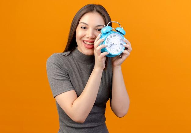 Radosna młoda ładna kobieta trzyma budzik na białym tle na pomarańczowym tle z miejsca na kopię