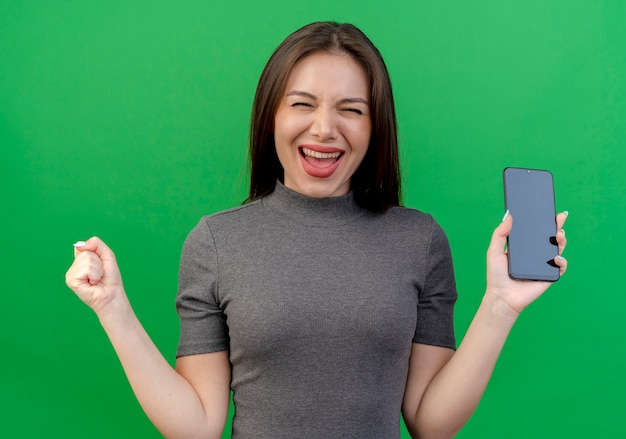 Radosna młoda ładna kobieta trzyma telefon komórkowy i zaciskając pięść na białym tle na zielonym tle